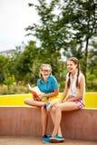 Los mejores amigos están leyendo el libro divertido en parque Foto de archivo