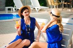 Los mejores amigos felices de las muchachas en día de fiesta que sorprende, beben los cócteles cerca de la piscina y de la divers fotografía de archivo