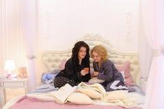 Los mejores amigos femeninos miran noticias en Internet en smartphone y cha Fotografía de archivo