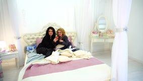 Los mejores amigos femeninos miran noticias en Internet en smartphone y charlan mientras que se sientan en cama en dormitorio bri metrajes