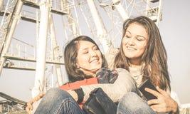 Los mejores amigos femeninos que disfrutan de la música que escucha de las novias del tiempo junta - en el teléfono Fotografía de archivo libre de regalías