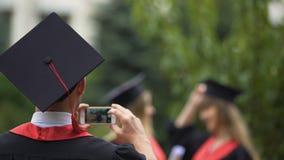 Los mejores amigos gradúan la presentación para la cámara, lanzando los casquillos de la graduación en el aire almacen de video
