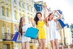 Los mejores amigos hacen compras Las muchachas que sostienen los panieres y caminan a Fotos de archivo libres de regalías