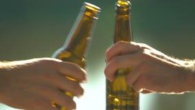 Los mejores amigos masculinos que celebran el cumpleaños, botellas de cerveza que tintinean al aire libre, alcohol almacen de video