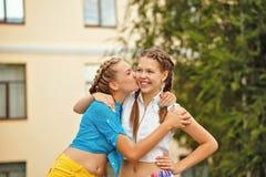 Los mejores amigos se besan en la mejilla en parque Imagen de archivo