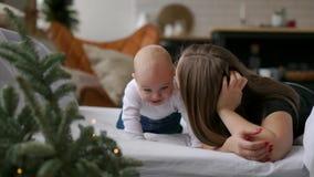 Los mejores momentos a partir de la vida, una madre joven feliz cariñosa abraza a un hijo de cuidado, en una manta blanca como la metrajes