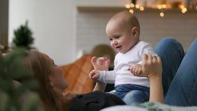 Los mejores momentos a partir de la vida, una madre joven feliz cariñosa abraza a un hijo de cuidado, en una manta blanca como la almacen de metraje de vídeo