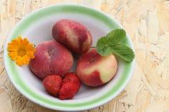 Los melocotones y la fresa maduros que mienten en una placa Foto de archivo libre de regalías