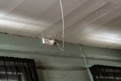 Los mercados eléctricos montaron en una pared de madera gastada rústica vieja con un cable eléctrico flojo que colgaba del techo  imagen de archivo libre de regalías