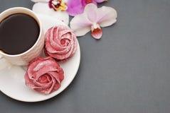 Los merengues y la taza de café rosados dulces en fondo del gris azul con la orquídea florece Fondo de la primavera con el espaci Foto de archivo