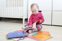 Los 10 meses lindos de bebé leen los libros en casa Imágenes de archivo libres de regalías