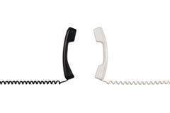 Los microteléfonos blancos y negros se arreglan verticalmente hacia uno a Fotografía de archivo libre de regalías