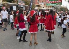 Los miembros del grupo de ayuda vestidos como Santa Claus entretienen a participantes y los visitantes del ` anual Cristmas de la Fotografía de archivo
