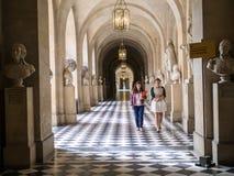 Los miembros del personal caminan abajo del pasillo del palacio de Versalles, Francia Fotografía de archivo libre de regalías