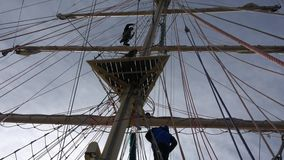 Los miembros f del equipo que navegan la nave alta están subiendo el palo en luz trasera para entrar en las yardas y para prepara almacen de metraje de vídeo