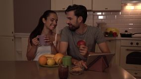 Los miembros felices de la pequeña familia se sientan en la tabla Bebidas de la muchacha de la taza El individuo come la manzana  almacen de video