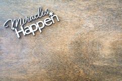 Los milagros de la inscripción suceden en un fondo de madera Concepto de inspiración y de esperanza imagen de archivo libre de regalías