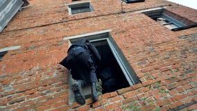 Los militares de las fuerzas especiales sobran una posición en un edificio de ladrillo metrajes