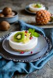 Los mini pasteles de queso crudos remataron con la piña, el kiwi y la granada Fotografía de archivo libre de regalías