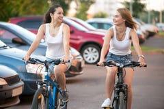 Los modelos adolescentes de risa compiten en las bicicletas Foto de archivo libre de regalías