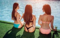 Los modelos asombrosos y bien hechos se sientan en el borde de la piscina Ellos piernas de los controles en agua Mirada de las mu fotos de archivo