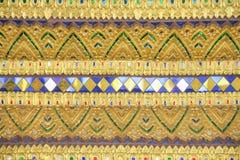 Los modelos de oro de la pintura texturizan el fondo en templo tailandés foto de archivo