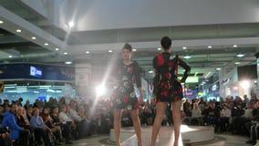 Los modelos en prolongación del andén, muchachas profanan en los vestidos negros y rojos, desfile de moda, modelo caminando en pr almacen de metraje de vídeo