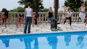Los modelos están ejercitando con la piscina en frente y el mar en fondo almacen de video
