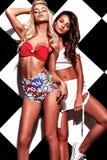 Los modelos morenos y rubios en rnb diseñan la ropa que presenta cerca de la pared del ajedrez Fotografía de archivo