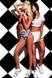 Los modelos morenos y rubios en rnb diseñan la ropa que presenta cerca de la pared del ajedrez Imagen de archivo