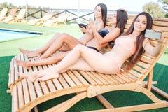 Los modelos se sientan en sunbeds y tienen cierto resto la primera que mujer joven sostiene el teléfono y que toma el selfie Segu fotografía de archivo libre de regalías