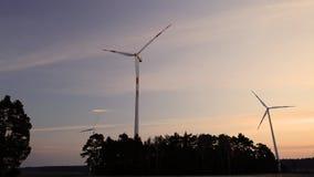Los molinoes de viento eléctricos accionan la silueta del generador en la puesta del sol almacen de video