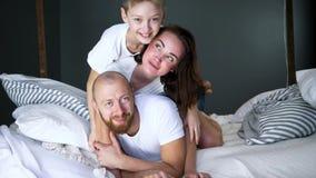 Los momentos felices, los padres jovenes con el hijo se divierten junto en cama en casa en sitio metrajes