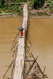 Los monjes budistas cruzan el río de Nam Khan en un puente de bambú, protegiéndose contra el sol con los paraguas, Luang Prabang, Fotografía de archivo