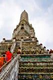 Los monjes budistas recorren encima de las escaleras del templo de Wat Arun en Bangkok Foto de archivo libre de regalías