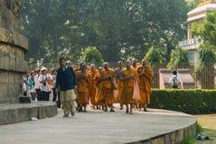 Los monjes budistas, seguidos por los peregrinos, circundan el Dhamekh Stupa Imagen de archivo libre de regalías