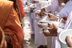 Los monjes de las limosnas budistas de Sanghagive a un monje budista imagenes de archivo
