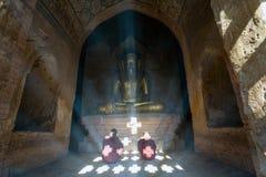 Los monjes del niño ruegan dentro de una pagoda - Bagan, Myanmar Imagenes de archivo