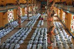 Los monjes ruegan en Cao Dai Temple.  Tay Ninh. Vietnam Imagen de archivo libre de regalías