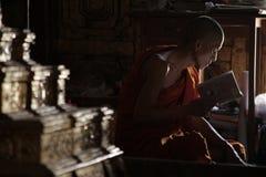 Los monjes se sentaron reservado leyendo el libro imagenes de archivo