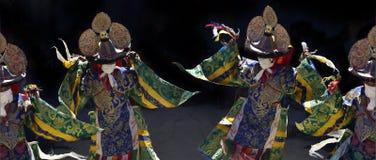 Los monjes tibetanos con las caras cerradas en ropa ritual festiva del brocado y de los sombreros sacros con los cráneos realizan Fotos de archivo libres de regalías