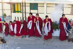 Los monjes tibetanos que arquean con incienso fuman para acoger con satisfacción al monje de alto nivel en el área del monasterio Foto de archivo libre de regalías