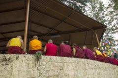 Los monjes tibetanos se están sentando debajo del tejado fotos de archivo libres de regalías