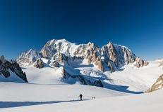 Los montañeses del esquí ascienden el glaciar de Vallee Blanche En backgroun Imágenes de archivo libres de regalías