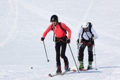 Los montañeses del esquí del equipo suben en la montaña en los esquís atados con correa a las pieles que suben Fotos de archivo