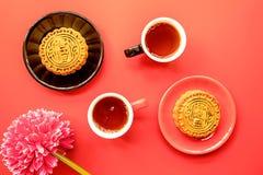 Los mooncakes del chino tradicional con té y las decoraciones en plano rojo del fondo ponen la visión superior imágenes de archivo libres de regalías
