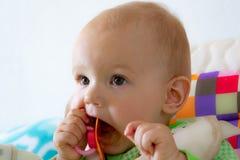Los mordiscos de un año/chupan del bebé en una entrerrosca de goma porque se están cortando sus dientes Pequeño muchacho alegre e imagen de archivo