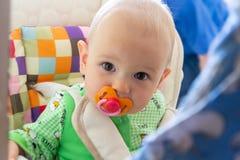 Los mordiscos de un año/chupan del bebé en una entrerrosca de goma porque se están cortando sus dientes Pequeño muchacho alegre e foto de archivo libre de regalías