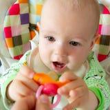 Los mordiscos de un año/chupan del bebé en una entrerrosca de goma porque se están cortando sus dientes Pequeño muchacho alegre e foto de archivo