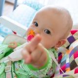 Los mordiscos de un año/chupan del bebé en una entrerrosca de goma porque se están cortando sus dientes Pequeño muchacho alegre e fotografía de archivo